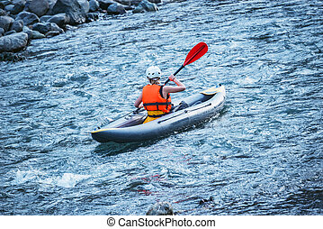 Young woman floats by inflatable boat on the mountain river.