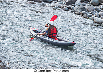 Young woman floats by inflatable boat.