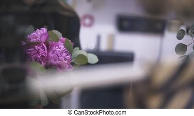 Young woman florist arranging a pink flower bunch in a shop