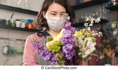 Young woman florist is holding bouquet of flowers standing in interior during pandemic.