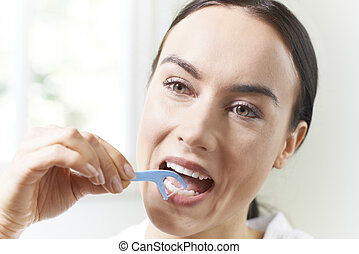 Young Woman Flossing Teeth In Bathroom