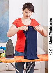 Young woman folding clothes