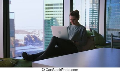 Young woman freelancer is sitting in window sill with skyscrapers view and working on her laptop
