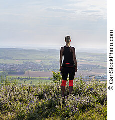 Young woman from back standing on lookout in fitness outfit looking to valley. Palava, Czech republic