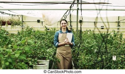Young woman gardener working in a large greenhouse. - Young...
