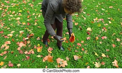 young woman gathering autumn leaves from ground