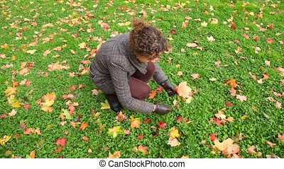 young woman gathering autumn leaves from ground in park