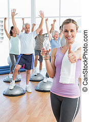 Young woman gesturing thumbs up with people stretching hands in the background at fitness studio
