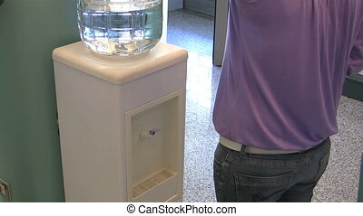 Young woman getting a cup of water from a water cooler. HD 30 fps