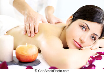 Strong hands doing massage on back of gorgeous female model in white spa during vacation relax
