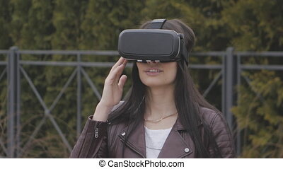 young woman getting experience in using VR-headset or virtual reality headset outdoor