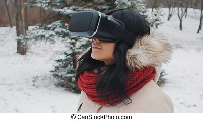young woman getting experience in using VR-headset outdoor at winter park
