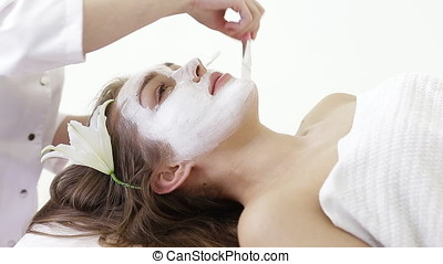 young woman getting facial massage in spa salon