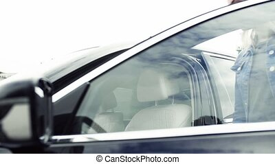 Young woman getting in car. Slow motion. - A young woman...