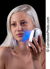 Young woman getting photo-therapy treatment with blue light