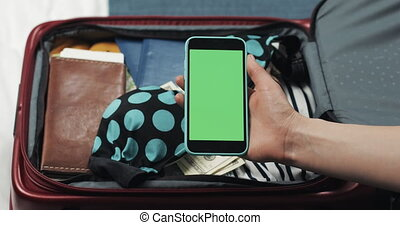 Young woman getting ready for a trip. She holding smartphone with green screen on the suitcase background. Chroma key.