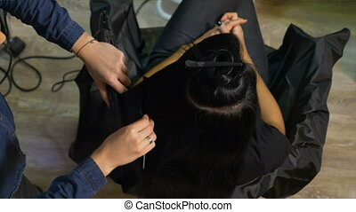 Young woman getting straight hair at beauty salon