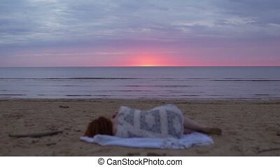 Young woman girl in a white dress laying in the foreground on a blanket and enjoying rare glowing nature sky - Amazing dark scenic vivid crimson rare red sunset