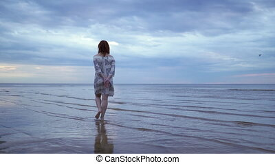 Young woman girl in a white dress standing and walking in...