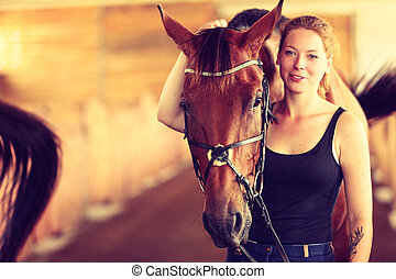 Young woman girl in stable with horse.