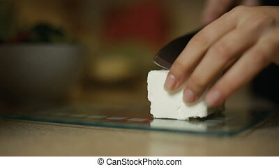 Young woman girl slices feta cheese on a glass board In the kitchen