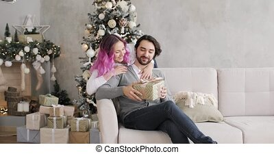 Young woman gives a gift to her husband in New Year's interior at home.