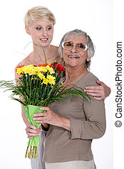 Young woman giving a senior lady a bunch of flowers