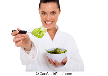 young woman giving fork with green salad