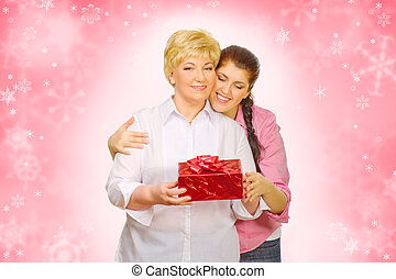 Young woman giving gift to her mother