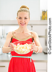 Young woman giving popcorn
