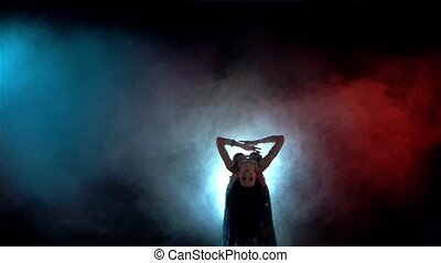Young woman go on belly dance in blue dress with long dark hair , back light, smoke, slow motion