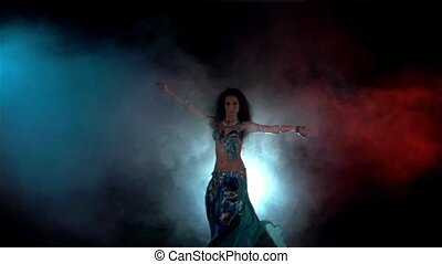 Young woman go on belly dance in blue dress with long dark hair , back light, red, blue, smoke, slow motion