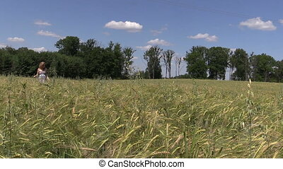young woman go through ripe rye field