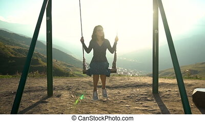 Young woman goes for a drive on a swing against a background...