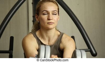 young woman goes in for sports, fitness at the gym. girl holding dumbbells and doing exercises