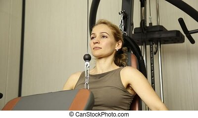 young woman goes in for sports, fitness at the gym. girl doing exercises on the simulator