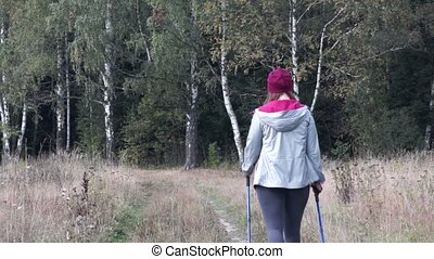 Young woman goes Nordic walking outdoors with small dog...