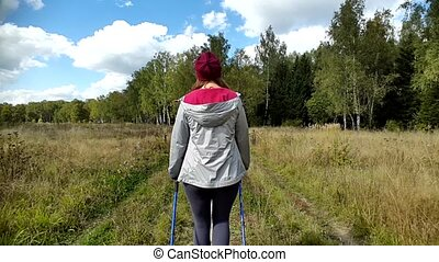Young woman goes Nordic walking outdoors