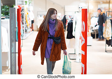 Young woman goes through a security anti-theft framework in a store.