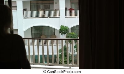 Young woman goes to balcony in lingerie - Young woman goes...