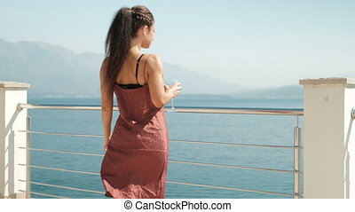 Young woman goes to pier with glass of wine.