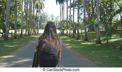 Young woman going along exotic parkland lane and viewing at...