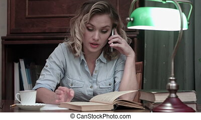 Young woman going through a book and having an angry phone conversation sitting at her desk