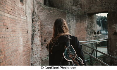 Young woman going through Roman Forum in Rome, Italy. Girl is capturing the beauty of old walls and enjoying the view.