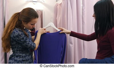 Young woman going to try on dresses in fitting rooms with help of assistant