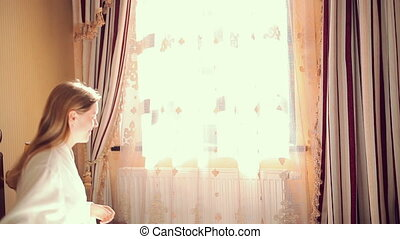 Young woman going to window