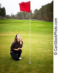 Young woman golf player on green, kissing ball