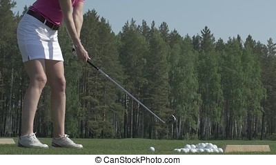 Young woman golf player training on green with club. Girl kick the ball
