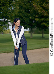 Young woman golfer in a sand bunker