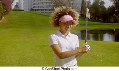 Young woman golfer in front of a lake on a course